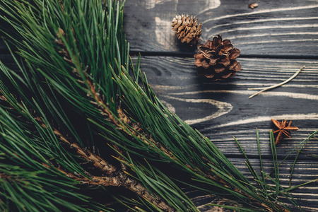 christmas tree branches with pine cones and anise on rustic background top view, space for text. stylish xmas seasonal greetings image. winter holidays mood. atmospheric still life