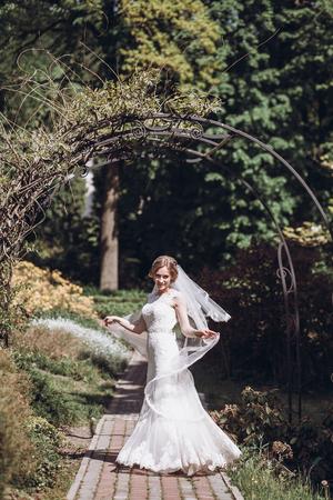 花のアーチでロマンティックな庭園で白いウェディング ドレスで渦巻く幸せな新婚の花嫁 写真素材