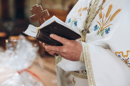 priest holding bible. holy book in hands of a man, praying in church at wedding matrimony. traditional religious wedding ceremony