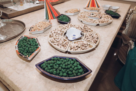 pistachio and salted nuts on tray on beer table at wedding reception in restaurant. luxury catering. christmas celebration