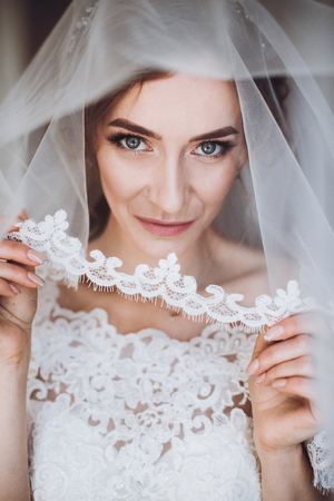 Beautiful blonde bride in elegant white lace wedding dress and veil holding sexy garter portrait, face closeup of gorgeous bride in hotel room Banco de Imagens