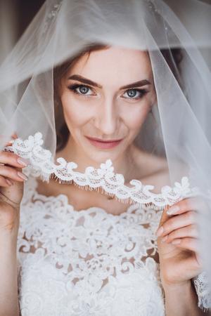 Mooie blonde bruid in elegante witte kant huwelijkskleding en sluier die sexy kousebandportret, gezichtsclose-up van schitterende bruid in hotelruimte houden