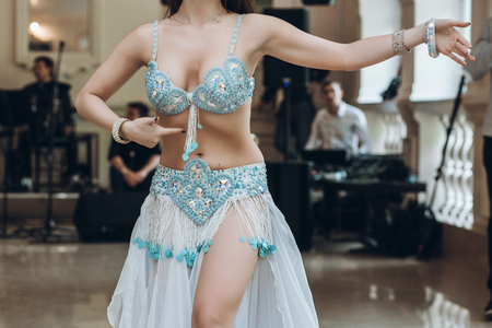 eastern dancing. sexy woman in blue costume performing eastern dance. belly dancer. beautiful woman dancing at wedding reception in restaurant