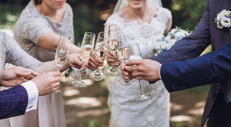 happy group of people toasting with champagne. hands holding glasses of champagne and clinking. bride bridesmaids and groom groomsmen having fun. holiday celebration. christmas feast