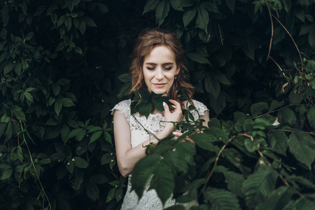beautiful gorgeous bride with green leaves portrait. woman posing in beautiful nature outdoors. happy wedding couple  posing at old castle. happy marriage moments. elopement concept
