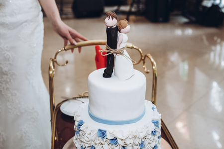 delicious wedding cake with blue flowers and figurines on top, bride and groom tied forever concept at wedding reception in restaurant. luxury catering. celebration, cake on tray
