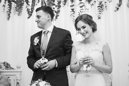 happy bride and groom with champagne glasses toasting at wedding reception. luxury decorated wedding centerpiece with purple flowers