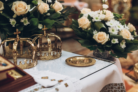 golden crowns and bible and wedding ring on altar in church at wedding matrimony. traditional religious wedding ceremony