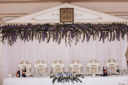 luxury decorated wedding centerpiece with purple flowers.  arrangement for bride and groom, table with chairs and food
