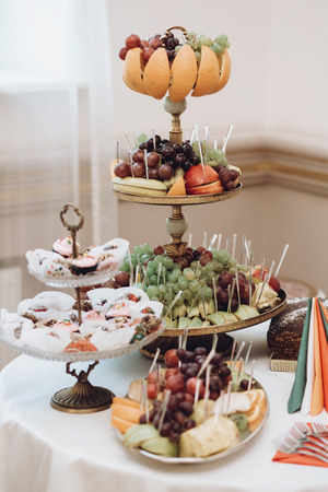 delicious fruits on stand and desserts sweet on table at wedding reception in restaurant. luxury catering. christmas feast. wedding candy bar