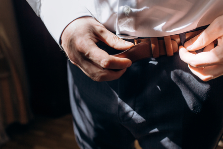Groom adjusting stylish brown leather belt during morning before wedding, handsome man in elegant suit putting on belt before meeting closeup