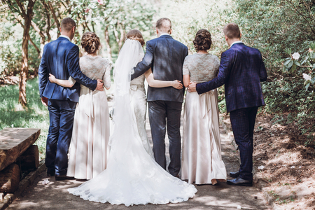 Happy wedding moment, newlywed bride and groom couple on a walk with bridesmaids and groomsmen, friends concept Stock Photo