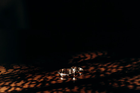 beautiful golden wedding rings on wooden table in morning sunlight. space for text. wedding concept