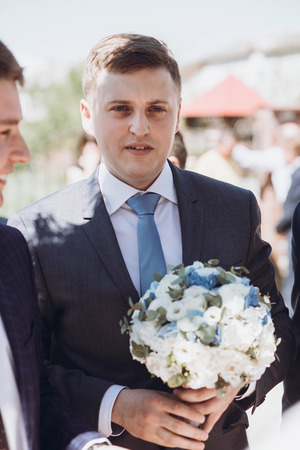 Handsome groom in elegant suit with wedding bouquet walking to church with groomsmen, wedding day concept Stock Photo