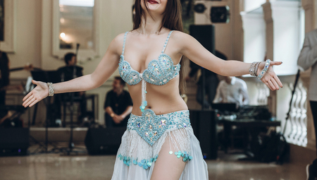 sexual belly dancer.  eastern dancing. woman in blue costume performing eastern dance.  beautiful woman dancing at wedding reception in restaurant. show program