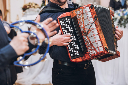 musicians playing on accordion and tambourine, musical band performing at wedding reception. fun time at party Stock Photo
