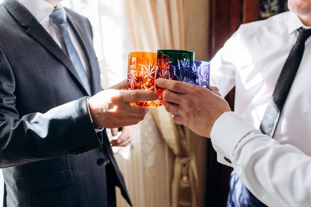 men hands holding colorful cups and toasting. happy groom with groomsmen having fun before wedding in the morning