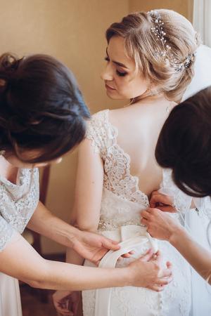 아름 다운 신부 들러리 결혼식 전에 고급 호텔 객실 아침에 화려한 금발 신부 웨딩 드레스에 넣어 도움이 스톡 콘텐츠