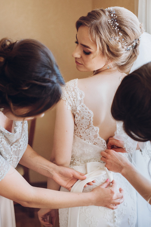 Beautiful bridesmaids help put on wedding dress on gorgeous blonde bride in luxury hotel room morning before the wedding Фото со стока - 88469289