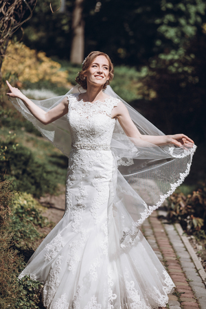 Happy newlywed bride swirling in white wedding dress in romantic garden with floral archway 版權商用圖片