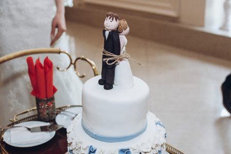 Funny wedding cake topper, figurines of bride and groom tied together with a rope, fun wedding moment with delicious white cake close-up, relationship concept