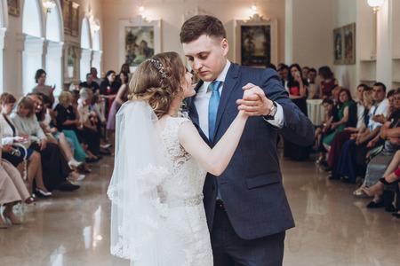 Los recién casados ??románticos bailan primero en el lugar del restaurante de lujo, la novia y el novio felices bailando en el hall del hotel, el momento de la boda sensual en la recepción, los invitados animando en el fondo Foto de archivo - 88370898