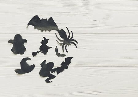 halloween flat lay. happy halloween concept, space for text. witch ghost bats and spider black decorations on white wooden background top view. simple cutouts for  holiday celebration. seasonal greetings