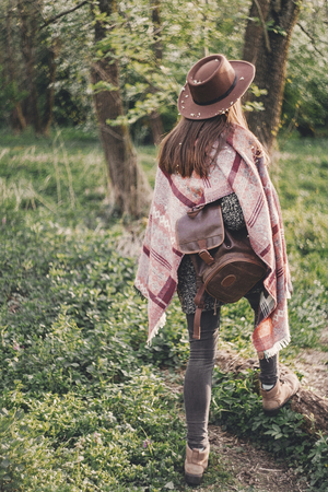 stylish hipster girl in hat with backpack walking in woods in evening sunshine. woman traveler back view in sunlight among trees. space for text. wanderlust. atmospheric moment
