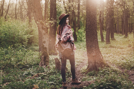 stylish hipster traveler girl in hat with backpack walking in woods in evening sunshine. bohemian fashionable woman exploring in sunlight. space for text. atmospheric moment. wanderlust