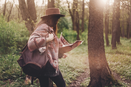 stylish hipster traveler girl in hat with backpack exploring in woods in amazing evening sunshine light. woman relaxing in sunlight. space for text. atmospheric moment. wanderlust