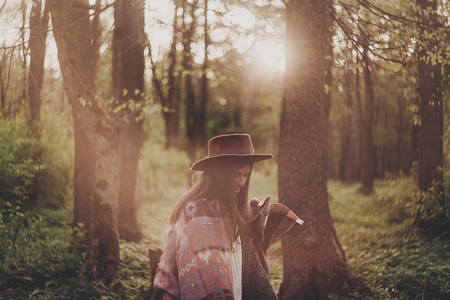 stylish hipster traveler girl in hat with backpack exploring in woods in amazing evening sunshine light. happy woman  in sunlight. space for text. atmospheric moment. wanderlust Imagens