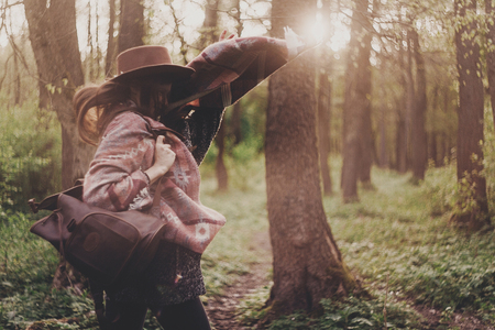 stylish hipster traveler girl in hat with backpack exploring in woods in amazing evening sunshine light. woman having fun jumping in sunlight. space for text. atmospheric moment Imagens