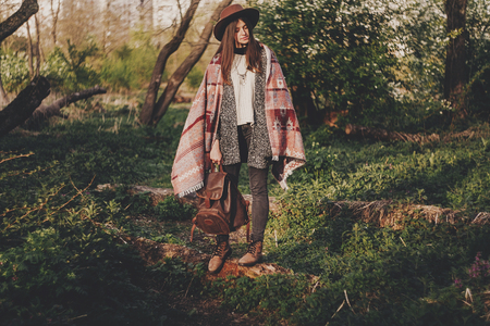 stylish hipster girl in hat and poncho holding backpack relaxing in woods in evening sunshine. bohemian fashionable woman traveler in sunlight. space for text. calm atmospheric moment