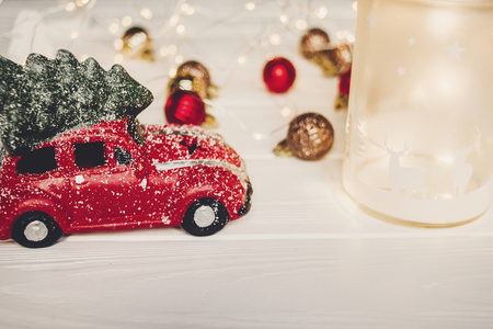 red car toy with christmas tree on top and lantern with deers on white wood with lights in background, space for text. christmas present. seasonal greetings. happy holidays. xmas gift