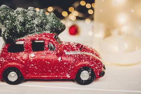 christmas present. red car toy with christmas tree on top on white wood with lights in background, space for text. seasonal greetings. happy holidays. xmas gift. holiday celebration