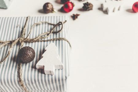 das stilvolle Weihnachten, das eingewickelt wird, stellt sich mit Verzierungen und Spielwaren auf Draufsicht des weißen hölzernen Hintergrundes, Raum für Text dar. Konzept der frohen Weihnachten. saisonale Grußkarte. schöne Ferien Lizenzfreie Bilder