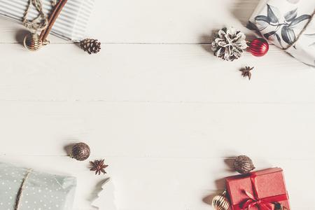 kerst plat lag. presenteert met ornamenten en dennenappels anijs op witte houten achtergrond bovenaanzicht, ruimte voor tekst. stijlvol ingepakte cadeaus. seizoensgebonden wenskaart. fijne vakantie Stockfoto