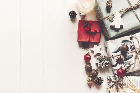 regalos envueltos de la Navidad moderna con los ornamentos y los conos en la opinión superior del fondo de madera blanco, texto del espacio. concepto de feliz Navidad. saludos estacionales. Felices fiestas, Navidad plana Foto de archivo