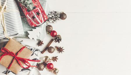 Navidad plana endecha. regalos envueltos con el anís de los conos del juguete y del pino del coche de los ornamentos en la opinión superior del fondo de madera blanco rústico, espacio para el texto. regalos elegantes saludos estacionales. felices vacaciones Foto de archivo