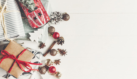 christmas flat lay. wrapped presents with ornaments  car toy and pine cones anise on rustic white wooden background top view, space for text. stylish gifts. seasonal greetings. happy holidays