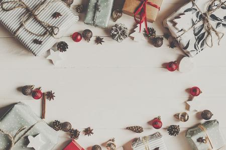 크리스마스 플랫 누워 mock 최대. 장식품과 소나무 콘 선물 상자 흰색 나무 배경에 상위 뷰, 텍스트위한 공간입니다. 세련 된 래핑 된 선물입니다. 계절