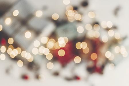 Konzept der frohen Weihnachten. unscharfe Lichter und Geschenke mit Verzierungen auf rustikalem weißem hölzernem Hintergrund, Raum für Text. saisonale Grußkarte. Frohe Feiertage und neues Jahr