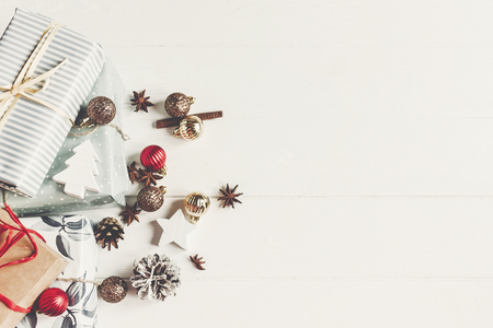 christmas flat lay. wrapped presents with ornaments and pine cones anise on rustic white wooden background top view, space for text. stylish gifts. seasonal greetings. happy holidays