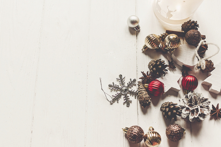 merry christmas concept, flat lay. modern ornaments anise cones and lights on rustic white wood top view, space for text. seasonal greetings. happy holidays. xmas card