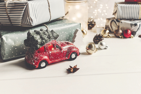 merry christmas and happy new year. modern presents, ornaments, car toy with tree,  anise cones and lights on rustic white wooden background. seasonal greetings. happy holidays, xmas card