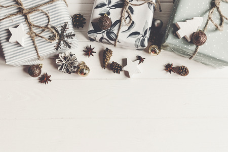 modern christmas flat lay composition. stylish wrapped presents with ornaments and  cones anise on rustic white wood, space for text, top view. seasonal greetings. happy holidays, xmas card
