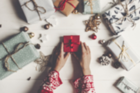 hands holding red present box on rustic white wood with gifts and ornaments, top view. merry christmas and happy new year flat lay. woman in red pajamas. seasonal greetings. blurred image