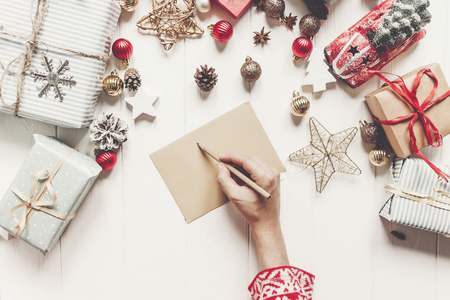 Hände, die Bleistift halten und eine Buchstabewunschliste zur Weihnachtsmann-Ebenenlage mit Platz für Text schreiben. Frohe Weihnachten und guten Rutsch ins Neue Jahr Draufsicht. Handarbeit und Geschenke und Ornamente auf weißem Holz