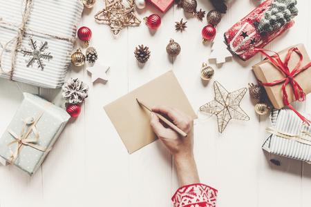 handen met potlood en het schrijven van een brief verlanglijstje voor de kerstman plat leggen met ruimte voor tekst. vrolijk kerstfeest en gelukkig Nieuwjaar bovenaanzicht. handwerk en geschenken en ornamenten op wit hout Stockfoto