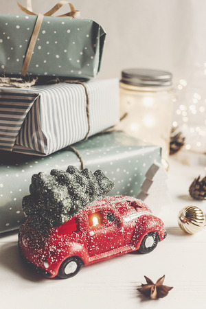 modern christmas ornaments and car toy with tree, presents cones anise on white wooden background. merry christmas concept. seasonal greetings. happy holidays, xmas card, hygge Stockfoto